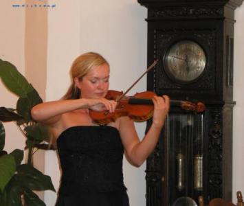 kobieta w czarnej sukience gra na skrzypcach