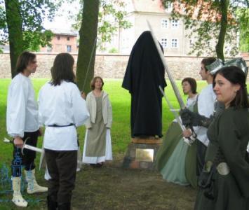grupa młodych ludzi w przebraniach obok pomnika przysłoniętego czarnym materiałem