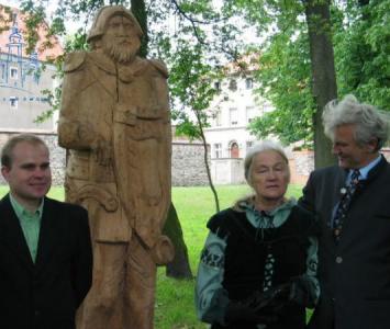 trójka ludzi stojąca obok drewnianego pomnika średniowiecznego woja
